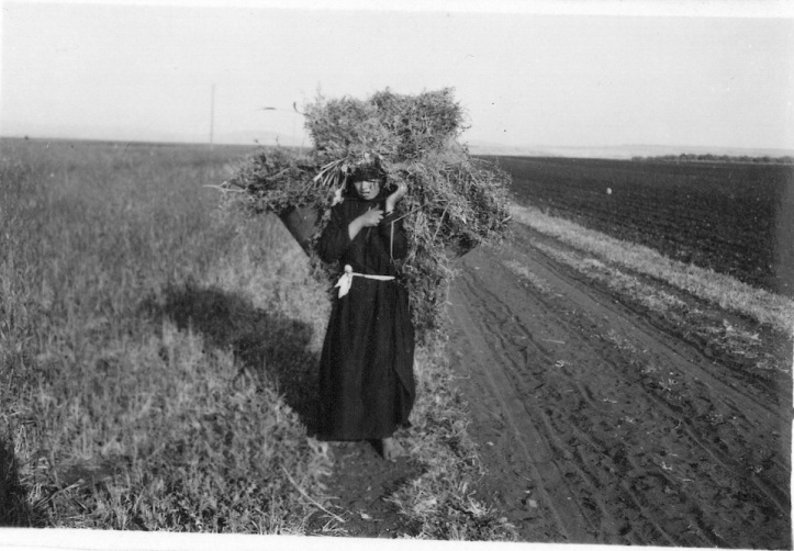 Native woman carrying weeds for fuel