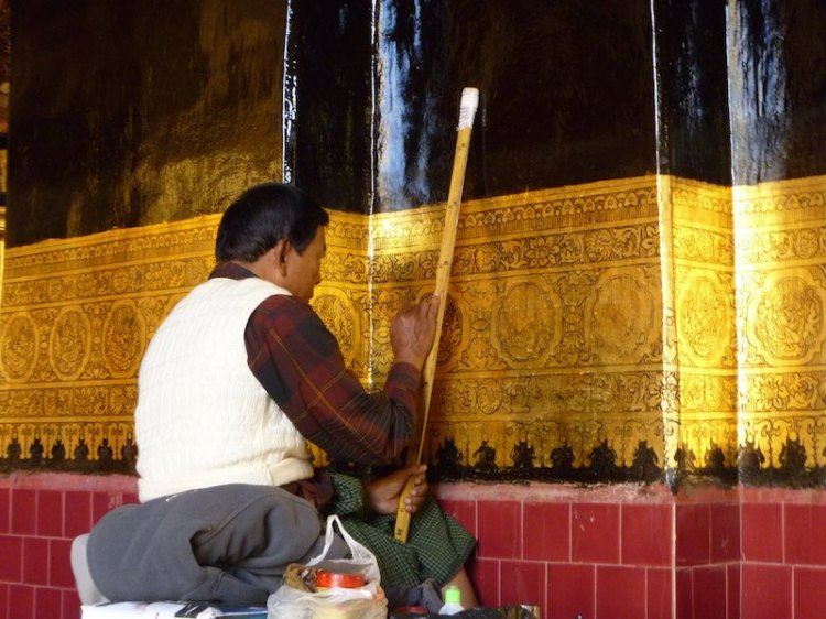 Painting over the freshly applied gold leaf at Mahamuni Buddha Temple