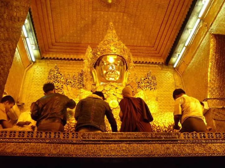 These men are applying gold leaf offerings to the Mahamuni Buddha in Mandalay