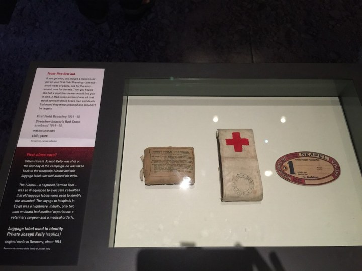 Wording as per the sign on the cabinet - Front-line first aid If you got shot, you prayed a mate would put on your First Field Dressing - just two small wads of gauze, one for the entry would, one for the exit.  Then you hoped like hell a stretcher-bearer would find you in time.  A Red Cross armband was all that stood between those brave men and death.  It showed they were unarmed and shouldn't be targets. First-class care? When Private Joseph Kelly was shot on the first day of the campaign, he was taken back to the troopship Lutzow and this baggage label was tied around his wrist.   The Lutzow - a captured German liner - was so ill-equipped to evacuate casualties that old luggage labels were used to identify the wounded.  The voyage to hospitals in Egypt was a nightmare.  Initially, only two men on board had medical experience: a veterinary surgeon and a medical orderly.